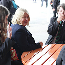 Students laughing around a table with a teacher